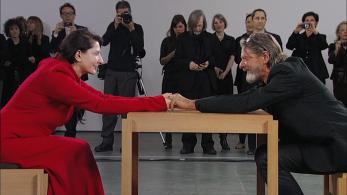 Umetnica Marina Abramović na svojem performansu, na katerem je sedela za mizo in zrla ljudem, ki so se usedli pred njo, v oči. Med obiskovalci je bil tudi njen dolgoletni bivši partner, česar ni vedela. Srečanje njunih pogledov je bil najganljivejši trenutek njenega celotnega performansa. Obema so tekle solze, segla sta drug proti drugemu in se prijela za roke. Vztrajala sta v pogledu iz oči v oči. Nista pobegnila v nezavednost. Vztrajala sta v budnosti in sprejemanju tega, kar je.